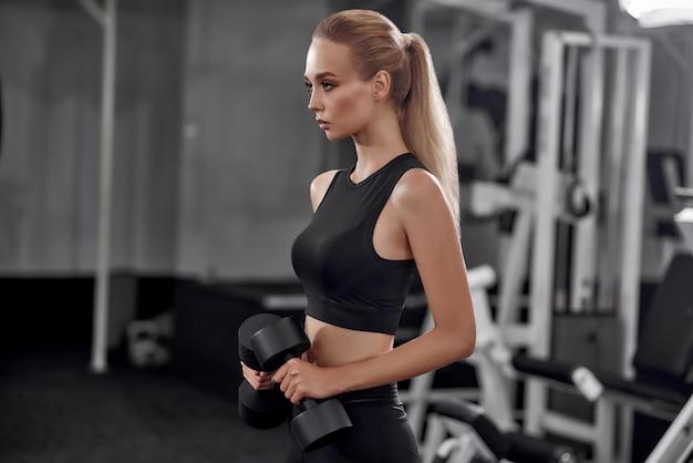 Zmotywowana blondynka podnosząc hantle w siłowni.