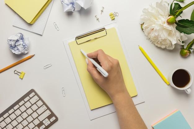 Zmotywowana młoda kobieta planuje strategię i pisze w zeszycie