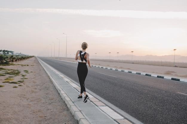 Zmotywowana niesamowita kobieta z tyłu biegająca po drodze w słoneczny poranek. trening, trening, prawdziwe emocje, zdrowy tryb życia, pracowita, silna sportsmenka, tropikalny kraj.