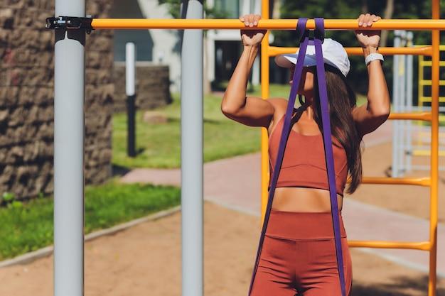 Zmotywowana, skoncentrowana wysportowana kobieta uprawiająca sport, trenująca, ćwicząca z gumowym paskiem, wykorzystująca elastyczną linę do rozciągania mięśni i treningów siłowych.