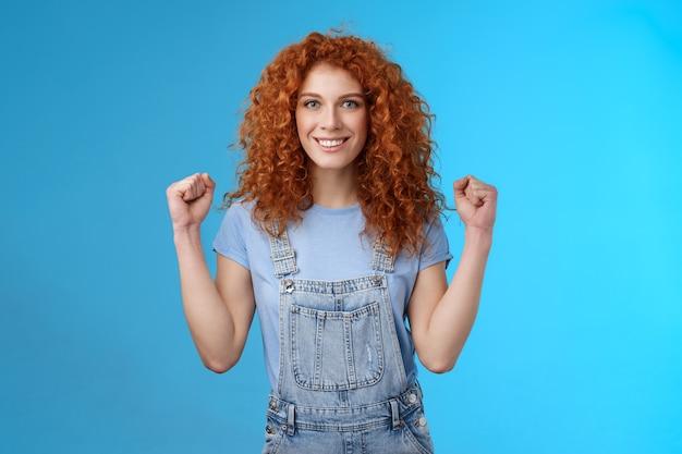 Zmotywowana zdeterminowana pewna siebie atrakcyjna rudowłosa wesoła dziewczyna zaciskająca pięści silna kobieta zapewniała, że wszystko poszło dobrze szczęśliwy letni dzień uśmiechnięta zachwycona pewna siebie na niebieskim tle.