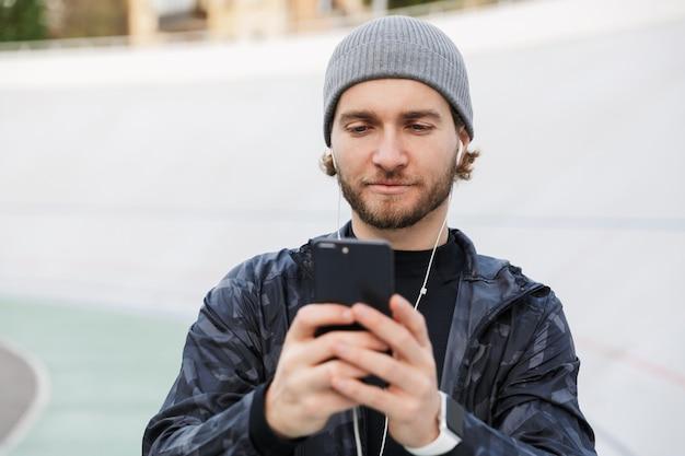 Zmotywowany młody sportowiec słuchający muzyki przez słuchawki stojąc na stadionie, używający telefonu komórkowego