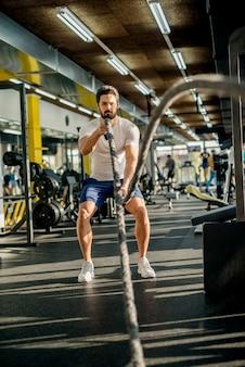 Zmotywowany skoncentrowany mięśni brodaty mężczyzna robi ćwiczenia liny bojowej w słonecznej nowoczesnej siłowni.