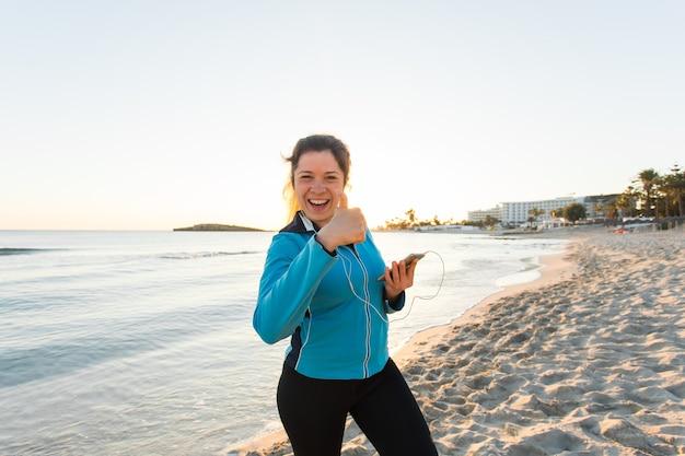 Zmotywowany sportowy kobieta robi kciuk w górę gest sukcesu po miejskim treningu na brzegu morza.