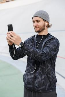 Zmotywowany uśmiechnięty młody sprawny sportowiec słuchający muzyki przez słuchawki stojąc na stadionie, robiący selfie z telefonu komórkowego