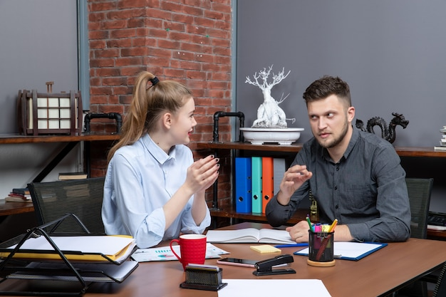Zmotywowany zespół zarządzający siedzący przy stole w sali konferencyjnej w środowisku biurowym