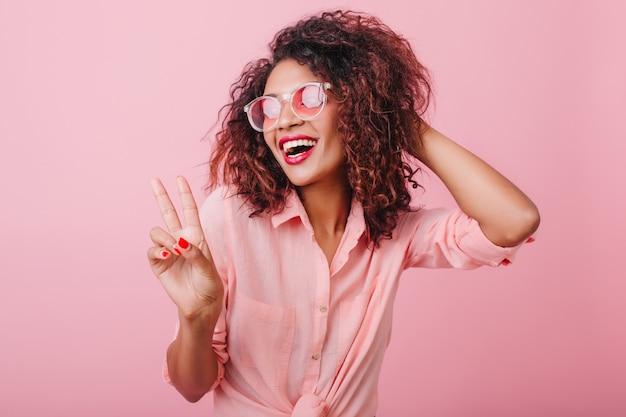 Zmysłowa afrykańska dama w modnym stroju vintage cieszącym się dobrym dniem. fascynująca, kochana kobieta w mrożących krew w żyłach okularach przeciwsłonecznych.