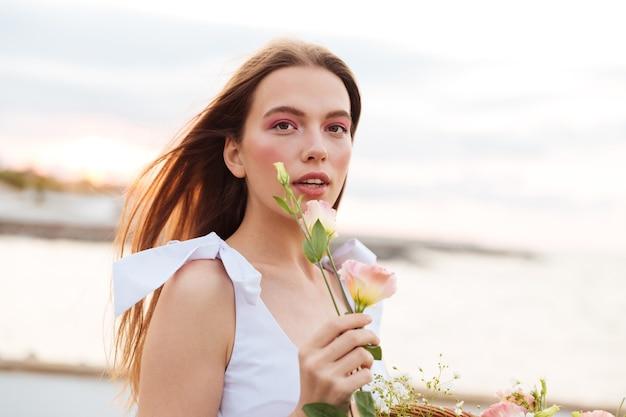 Zmysłowa atrakcyjna młoda kobieta stojąca na zewnątrz i trzymając kwiat