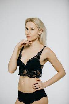 Zmysłowa blondynka piękna kobieta pozuje w eleganckiej czarnej bieliźnie