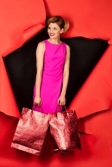 Zmysłowa blondynka w różowej sukience przechodzi przez czerwony papier. kobieta trzyma torby. niesamowita kobieta przechodzi przez czerwony papier. skopiuj miejsce na reklamę. modne ubrania. letnia wyprzedaż. zniżka.