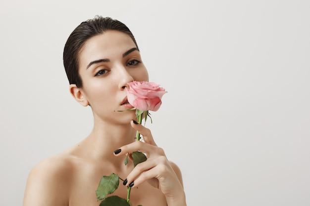Zmysłowa brunetka kobieta z różą stoi nago i wpatruje się w kamerę na szaro