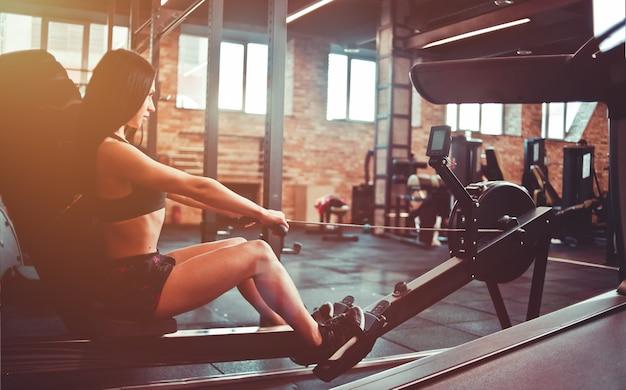 Zmysłowa brunetka w sportowym ubraniu siedząca na symulatorze wioślarskim. trening funkcjonalny