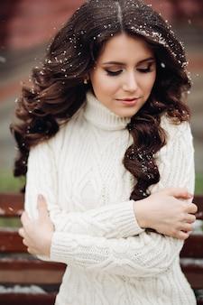 Zmysłowa brunetka z długimi falującymi włosami pokrytymi pierwszymi płatkami śniegu