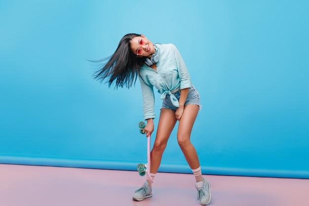 Zmysłowa ciemnowłosa dziewczyna tańczy, trzymając longboard w swobodnym stroju ulicznym. łapanie hiszpanin kobieta w trampkach pozuje z uśmiechem.
