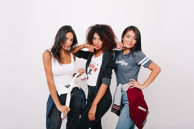 Zmysłowa czarna dziewczyna z kręconymi fryzurami pozuje między przyjaciółmi w stylowym stroju i patrzy z zainteresowaniem. cieszę się, że opalona azjatka spędza czas z kolegami z uniwersytetu i uśmiecha się.