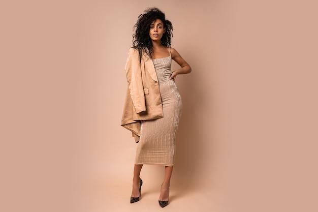 Zmysłowa czarna kobieta z pięknymi falującymi włosami w złotej błyszczącej sukience pozowanie. pełna długość.