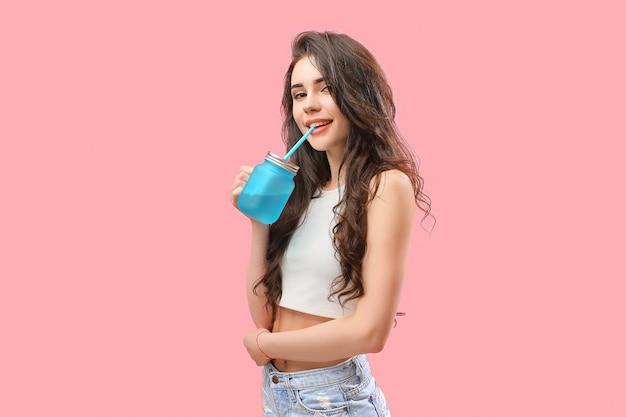 Zmysłowa dziewczyna w letnim stroju z napojem