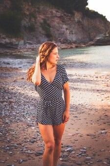 Zmysłowa dziewczyna w skalistej zatoczce ubrana w sukienkę w czarno-białe kropki