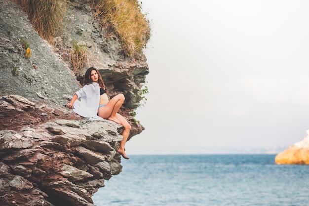 Zmysłowa dziewczyna w skalistej zatoczce w dużej białej koszuli i bikini.