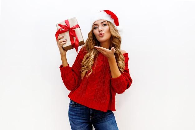 Zmysłowa dziewczyna z lśniącymi blond falującymi włosami przesyła buziaka. moda zimowa. strój noworoczny. wysyła pocałunek w powietrze