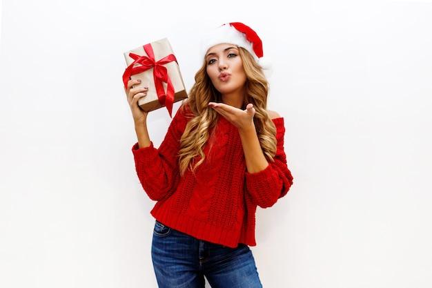 Zmysłowa dziewczyna z lśniącymi blond falującymi włosami przesyła buziaka. modny zimowy wygląd. strój noworoczny