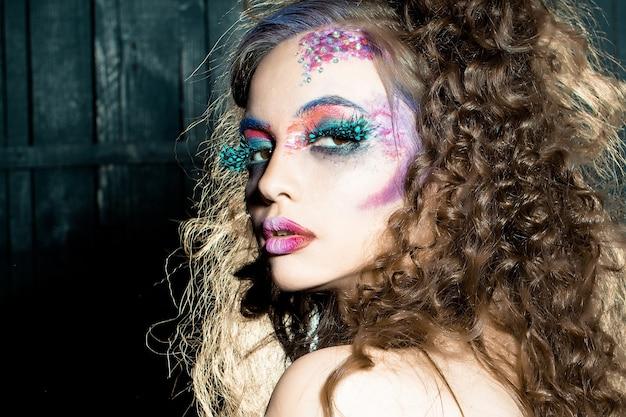Zmysłowa dziewczyna z paited face sztuka składa się z seksownej kobiety z jasnym makijażem i modnymi rzęsami z piór