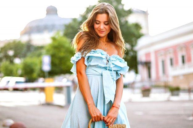 Zmysłowa elegancka modelka pozująca na ulicy w niebieskiej kobiecej sukience