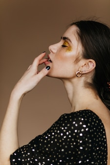Zmysłowa europejska modelka nosi złote dodatki stojące na brązowej ścianie. wewnątrz zdjęcie uroczej czarnowłosej kobiety z błyszczącym makijażem.