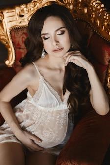 Zmysłowa i piękna młoda kobieta w ciąży model brunetka z jasnym makijażem w białej koronkowej bieliźnie siedzi na vintage czerwonym ze złotym fotelem i pozuje w luksusowym wnętrzu
