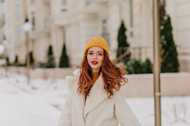 Zmysłowa imbirowa kobieta pozuje na ulicy rozmycie. kaukaski ładna dziewczyna korzystających z zimowych.