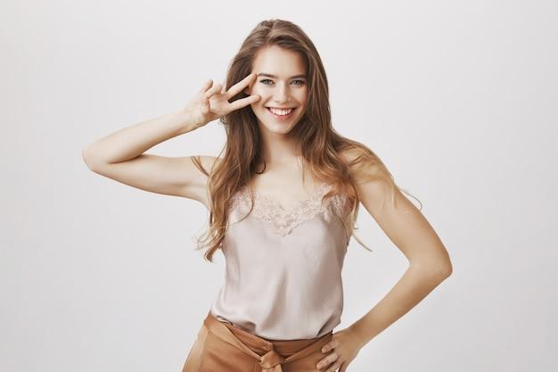 Zmysłowa kobieca kobieta pokazuje znak pokoju i uśmiecha się