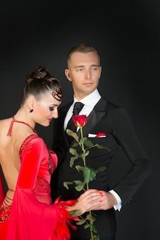 Zmysłowa kobieta i mężczyzna z kwiatem róży. kobieta w czerwonej sukience i macho w smokingu. para tancerzy w sali balowej w miłości. obchody walentynek. koncepcja miłości propozycji i daty.