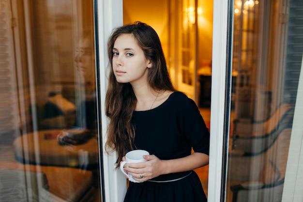 Zmysłowa kobieta w drzwi balkonowe