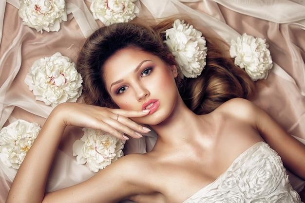 Zmysłowa kobieta w modnej sukni leżącej w kwiaty