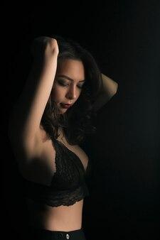 Zmysłowa kobieta w seksownym koronkowym staniku w ciemnym studio