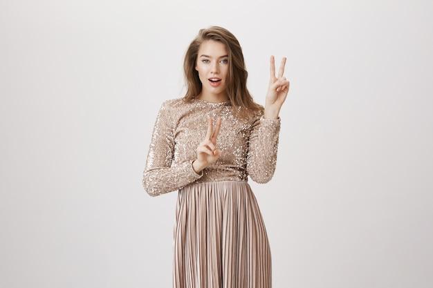 Zmysłowa kobieta w stroju wieczorowym pokazuje znaki pokoju