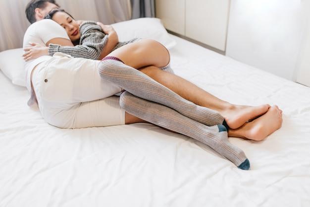Zmysłowa kobieta w szarych podkolanówkach śpi z mężem po ciężkim dniu