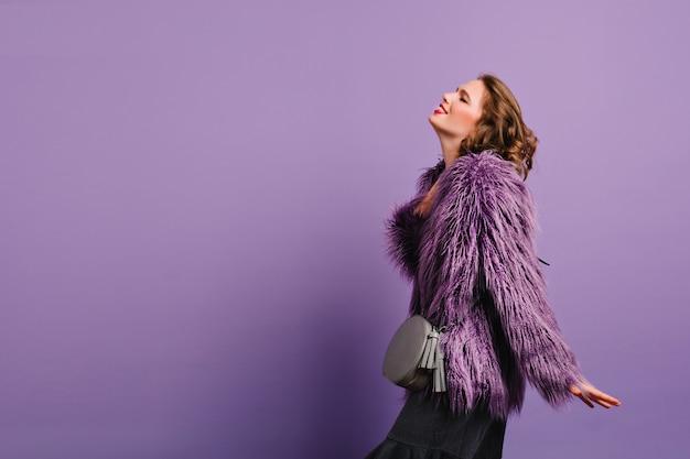 Zmysłowa kobieta z krótkimi ciemnymi włosami pozowanie w nowej fioletowej kurtce w studio
