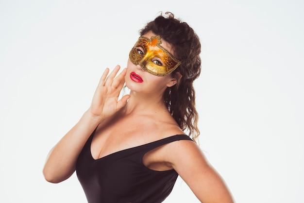 Zmysłowa ładna kobieta w złotej masce