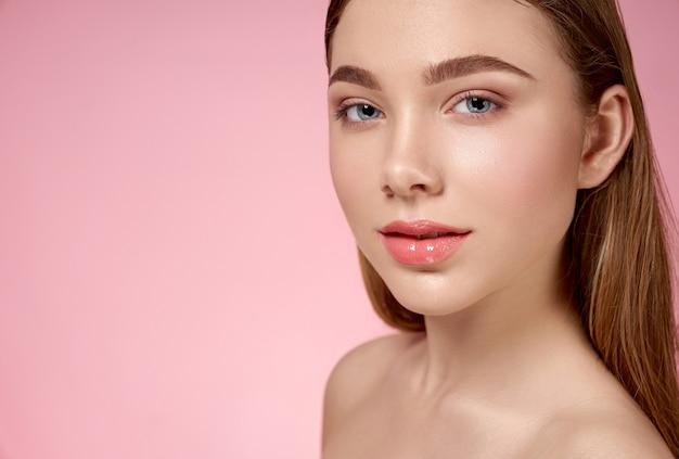 Zmysłowa, ładna, młoda dziewczyna o różowych, nagich ustach i zadbanej skórze twarzy pozuje na różowo