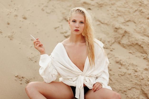 Zmysłowa młoda blondynka w białej dużej koszuli siedzi na ziemi piasku. pewna dziewczyna palenia na zewnątrz.