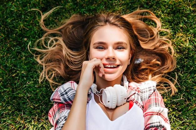 Zmysłowa młoda kobieta pozowanie na ziemi w parku. całkiem uśmiechnięta dziewczyna leżąca na trawie.