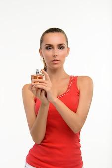 Zmysłowa młoda kobieta trzyma butelkę perfum.