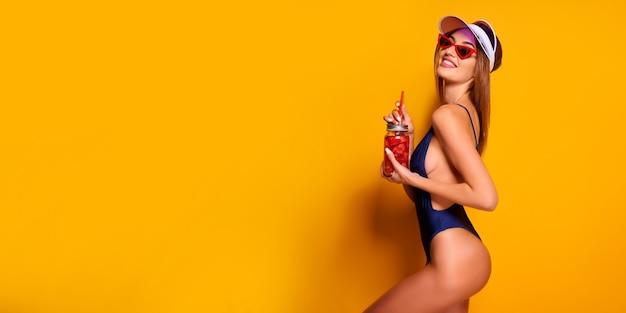 Zmysłowa młoda kobieta w letnim stroju, czapce, okularach przeciwsłonecznych trzymając słoik ze świeżym napojem i stojąc na jasnożółtym tle