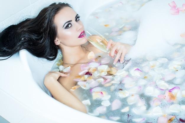 Zmysłowa młoda naga kobieta ciało w wannie seksowna dziewczyna relaks w wannie atrakcyjna, zmysłowa brunetka młoda kobieta z kieliszkiem wina w ręku leżąca w wannie z pianką i płatkami kwiatów róży