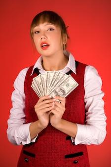 Zmysłowa młoda piękna dziewczyna w casual trzyma paczkę dolarów na czerwono