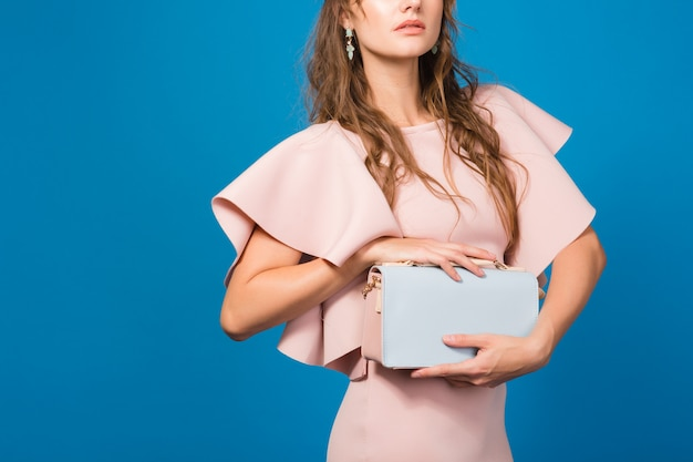 Zmysłowa młoda stylowa seksowna kobieta w różowej luksusowej sukience, letni trend w modzie, elegancki styl, trzymając modną torebkę