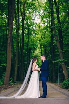 Zmysłowa para nowożeńców patrzących sobie w oczy, trzymając się za ręce