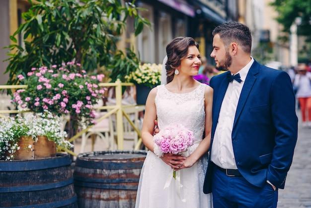 Zmysłowa para nowożeńców przytula się i patrzy sobie w oczy, trzymając się za ręce