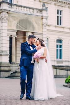 Zmysłowa para nowożeńców skłaniająca się do siebie i spacerująca